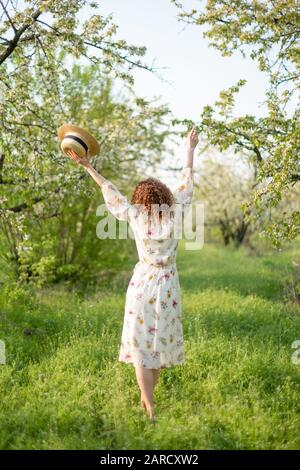 Young attractive woman with curly hair walking in a green flowered garden. Spring romantic mood. - Stock Photo