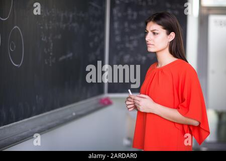 Pretty, young college student writing on the chalkboard/blackboard during a math class - Stock Photo