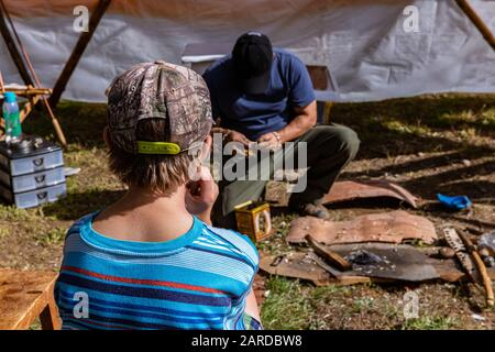 Rear view of boy in blue t-shirt with wearing cap and sitting by wooden bench. against man doing some artwork on lawn in event - Stock Photo