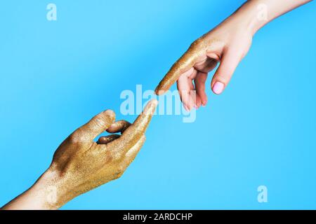 Hands of man and woman reaching to each other on blue background. - Stock Photo