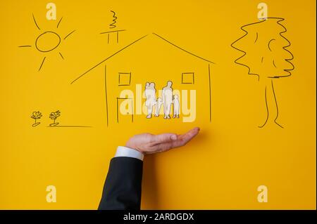 Male hand in a suit in supportive gesture under a hand drawn house with a paper cut silhouette of a family inside in conceptual image. Over yellow bac - Stock Photo