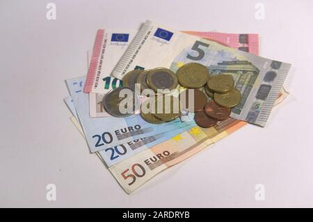 A lot of euro coins and cents on a few banknotes from twenty euros to fifty euros isolated on a blank table - Stock Photo