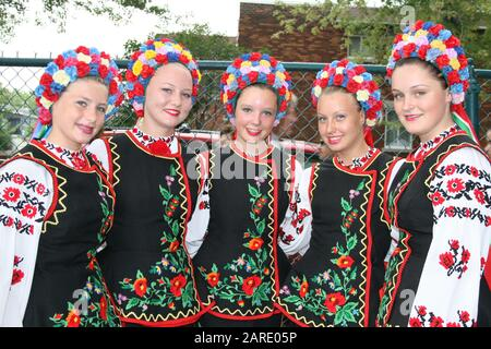 Smiling  dancers dressed in traditional red Ukrainian embroidered costume - Stock Photo