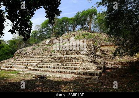 An overgrown step pyramid basks in the sunlight of the ancient Mayan city of Edzna, Mexico, gradually turning to rubble. - Stock Photo