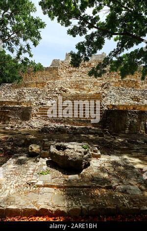 The overgrown ruins of a low step pyramid bask in the sunlight of the ancient Mayan city of Edzna, Mexico. - Stock Photo