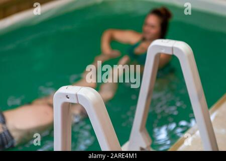 Closeup of swimming pool ladder with female therapist helping relaxed pregnant woman exercising in swimming pool in aqua therapy centre  - Stock Photo