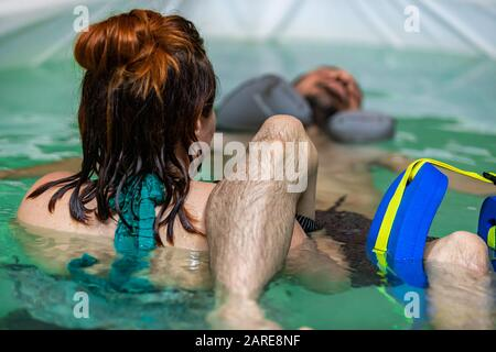 Rear view of a young female experienced therapist giving water therapy to young man on legs with leg support floats in swimming pool  - Stock Photo