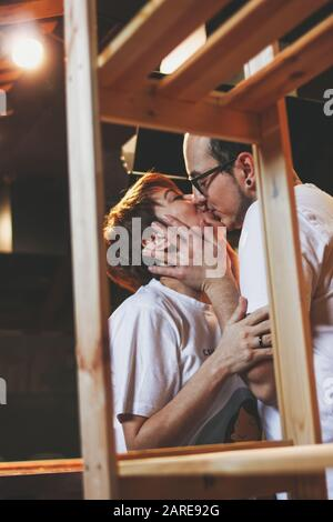 Happy young couple in love kissing and having fun together at home