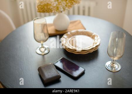 Dinnerware smartphone and wallet on table decorated with vase of flowers - Stock Photo