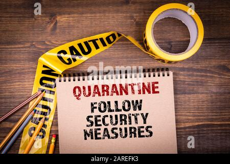 Quarantine. Follow security measures. Yellow plastic caution tape and a notepad on a wooden table - Stock Photo