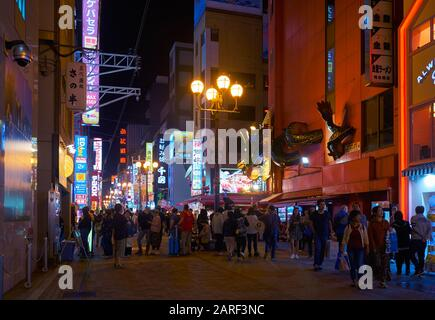 OSAKA, JAPAN - OCTOBER 13, 2019: The night view of people walking down the Dotonbori street full of neon lights, extravagant signage, and the enormous - Stock Photo