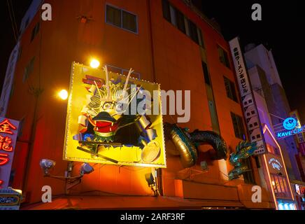 OSAKA, JAPAN - OCTOBER 13, 2019: The view of the famous gigantic Dragon sign on the wall of Kinryu Ramen Honten on the Dotonbori street in the night. - Stock Photo
