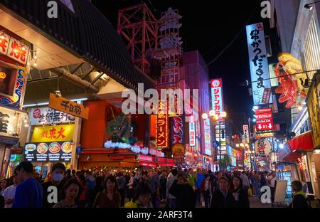 OSAKA, JAPAN - OCTOBER 13, 2019:  Night view of Dotonbori full of people walkin down the street with its famous bars and restorans with giant crab (Ka - Stock Photo