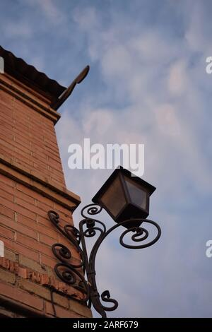 Street lantern made of black metal with forged curl pattern hang on the corner of house, blue sky background. - Stock Photo