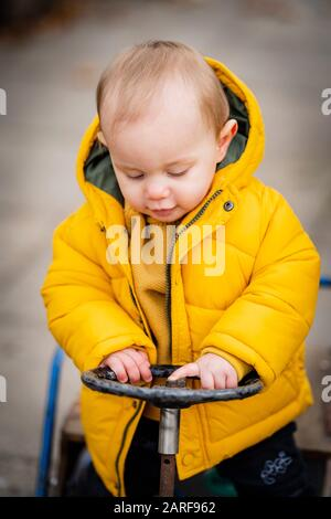 Baby boy of one year old driving a play toy cart and having fun.