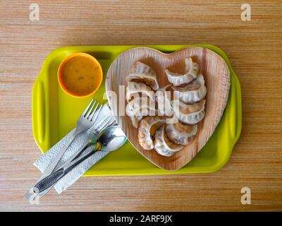 Momo served in a heart-shaped plate placed on a wooden surface. Stock Photo