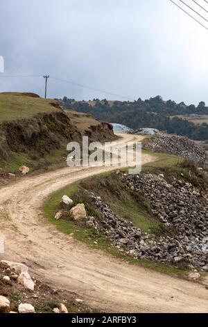 Curvy narrow dirt road in remote hilly region. - Stock Photo