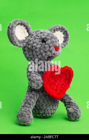 Grey knitted mouse with a heart in hand on a green background, side view. - Stock Photo