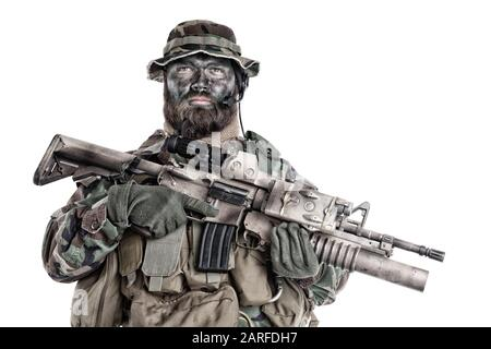 Serious commando fighter, military company mercenary with camouflage paint on bearded face, holding assault rifle with grenade launcher and laser - Stock Photo