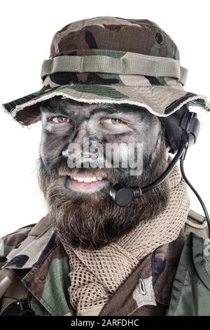 Shoulder studio portrait of commando soldier, modern mercenary, professional soldier with black camouflage paint on bearded face, tactical radio - Stock Photo