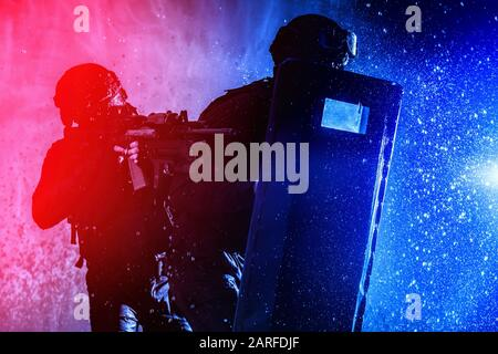 Counter terrorist squad members, police quick reaction, tactical group shooters, two SWAT officers hiding behind, covering themselves with ballistic - Stock Photo