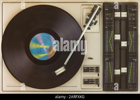 Retro styled view from above of a vintage turntable with spinning record - Stock Photo