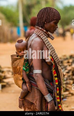 Hamer woman carrying baby on her back, Hamer tribe weekly market in Turmi, Omo Valley, Ethiopia. - Stock Photo
