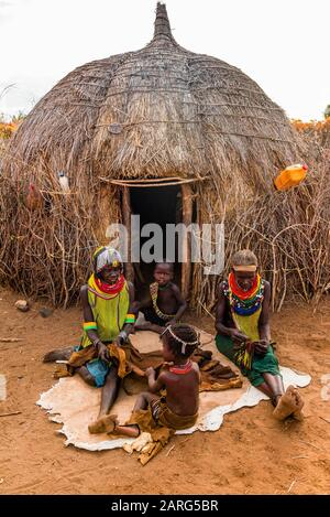 Nyangatom tribe women and children sit in front of their hut in their village, Omo Valley, Ethiopia. - Stock Photo