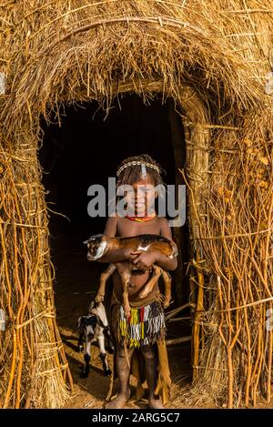Young Nyangatom tribe girl holding a goat in front of her hut, Omo Valley, Ethiopia. - Stock Photo