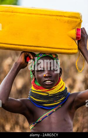 Nyangatom tribe people carrying water containers, Omo Valley, Ethiopia. - Stock Photo
