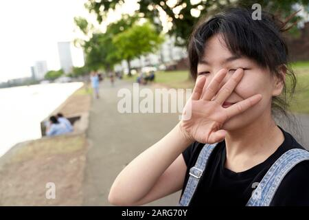 Korean woman looking at camera with hand covering face. Frankfurt am Main, Germany. - Stock Photo