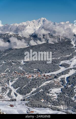 View across the valley towards the French ski resort of Meribel surrounded by pine forests in the 3 valleys ski area of France. - Stock Photo