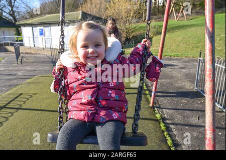 Brighton UK 28th January 2020 - 3 year old Isabella enjoys a ride on the swings in Queens Park Brighton with her mum pushing on a beautiful sunny but cold day in Britain . Credit: Simon Dack / Alamy Live News