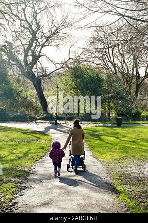 Brighton UK 28th January 2020 - A young mum and her children enjoy a walk through Queens Park in Brighton on a beautiful sunny but cold day in Britain . Credit: Simon Dack / Alamy Live News