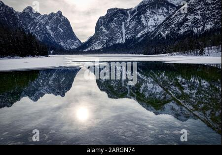 The sun is reflected in the cold waters of Lake Dobbiaco - Stock Photo