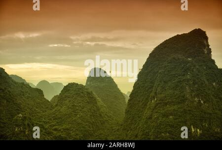 Hot air balloons flying over Karst mountain landscape in Chinese Guanxi province. - Stock Photo