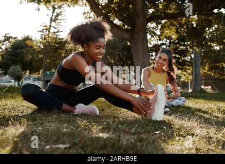 Smiling two diverse sporty fit young female friends stretching their legs in the park - african american black female warming up with her friend