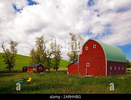 Big, red barn near rolling wheat fields on a partly sunny day in the Palouse area of Washington state - Stock Photo
