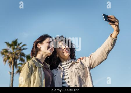 young interracial couple of women doing a selfie photo in a blue sky background with a mobile phone, concept of female friendship and racial diversity