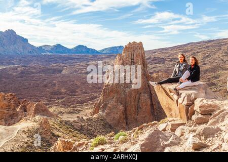 two young women sitting on rock outcrop high over teide national park tenerife