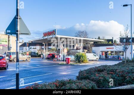 Sainsburys fuel station with vehicles queuing on a sunny winter late afternoon - Stock Photo