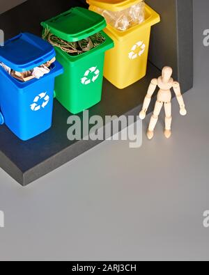 Wooden model of human and three color coded recycle bins, isometric projection with copy-space. Recycling sign on the bins, blue, yellow and green. Wa - Stock Photo