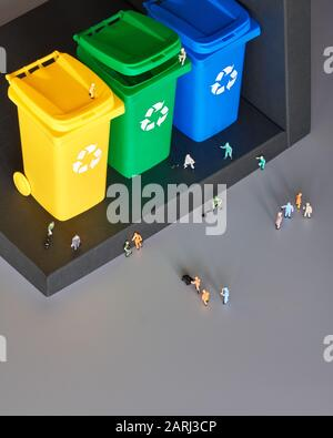 Miniature people, workers around three color coded recycle bins, isometric projection with copy-space. Recycling sign on the bins, blue, yellow and gr - Stock Photo