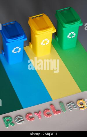 Three color coded recycle bins, isometric picture on geometric layered paper background. Recycling sign on blue, yellow and green containers. Waste se - Stock Photo