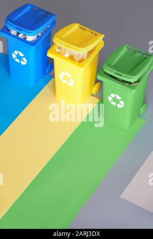 Three color coded recycle bins, isometric picture on geometric layered paper background. Recycling sign on blue, yellow and green bins. Waste separati - Stock Photo