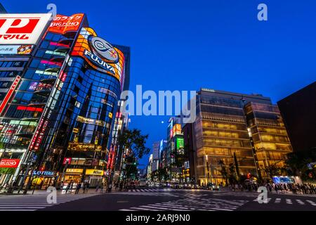 Night wide angle view of Sukiyabashi crossing in Ginza. Ginzia is considered one of the most expensive and luxury shopping districts in the world - Stock Photo