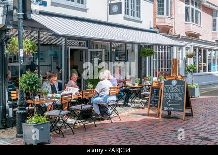 People sitting outside The Refinery coffee bar in Faversham, Kent. - Stock Photo