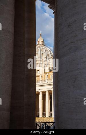 A view of St. Peters Basilica between the pillars of the colonnade around St. Peters Square, Vatican City. - Stock Photo