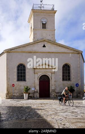 A cyclist cycles through the central squaire of Bois Plage en Re, Ile de Re, Charente-Maritime, France.  Cycling is a good way to explore the island. - Stock Photo