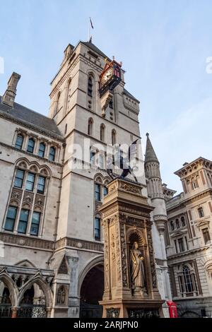 C.B. Birch's City of London Dragon statue is seen in front of the Royal Courts of Justice clock tower on Fleet Street, City of London, England, UK. - Stock Photo